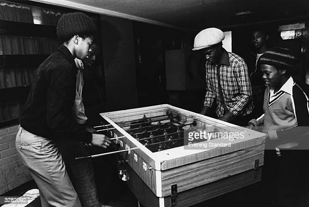 Youths play table football at the Metro Community Centre Notting Hill west London