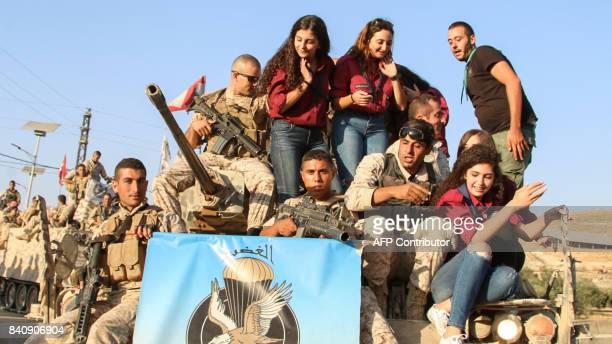 Youths ride on an armoured vehicle next to Lebanese Army soldiers during a celebration of their return from battling Islamic State group jihadists on...