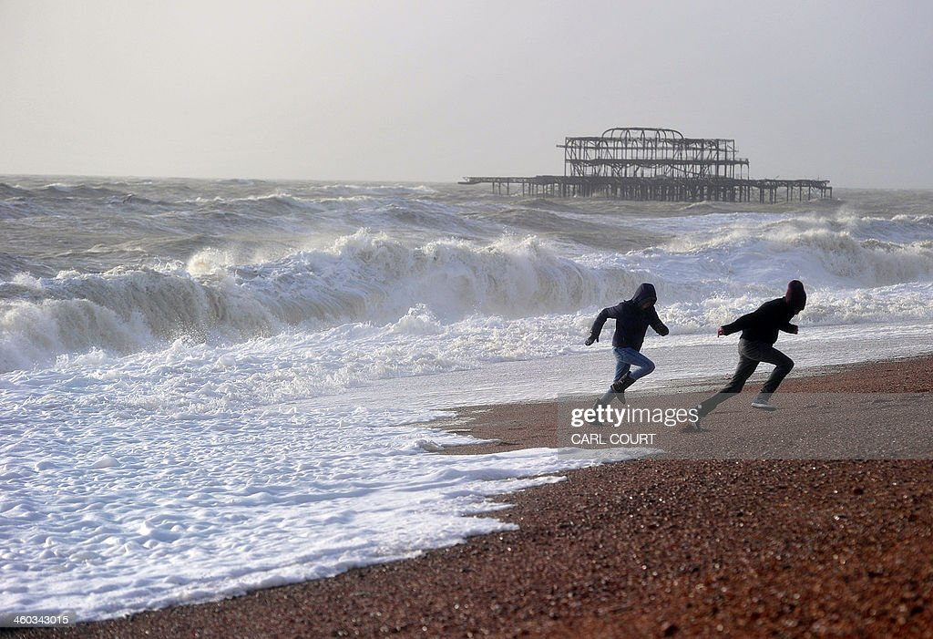 Youths run back from waves crashing onto the beach in Brighton in southern England on January 3 2014 after a high tide High tides and strong winds...