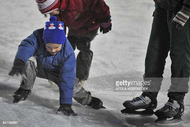 Youths skate on ice in front of the main building of 'Varosligeti Mujegpalya' an artificial outdoor icerink in 14th district of Budapest close to the...