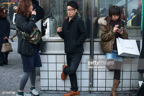 Youths smoking at a designated smaoking area at the Sibuya Crossing in Tokyo Special smoking areas have been designated and it is punishable by fine...