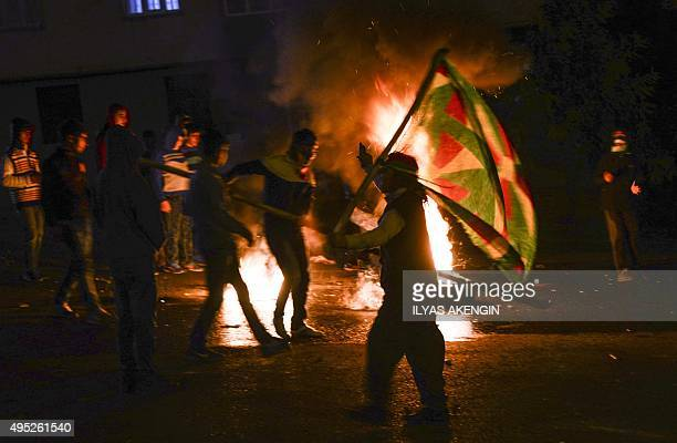 Youths stand near burning tires during clashes between Turkish riot police and Kurdish protesters in the southeastern city of Diyarbakir on November...
