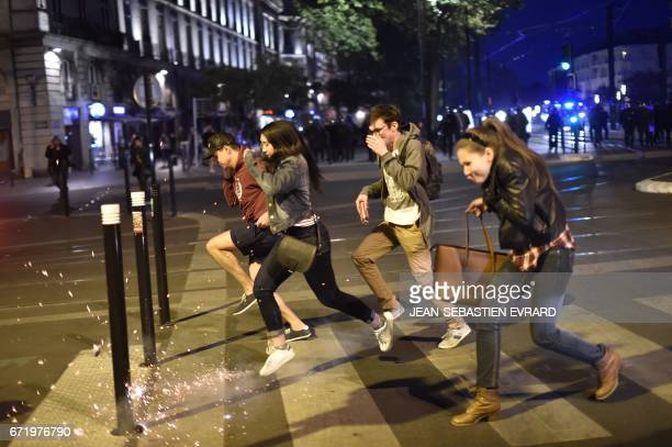 Youths try to avoid flares while crossing a street as antifascist demonstrators clash with antiriot police forces in Nantes western France on April...