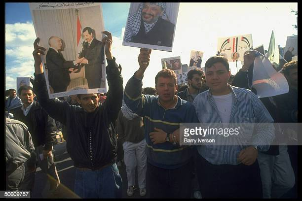 Youths w pics of PLO chmn Arafat Iraqi Pres Saddam Hussein shaking hands w King Hussein in mass proIraqi demo as outbreak of gulf war appears imminent