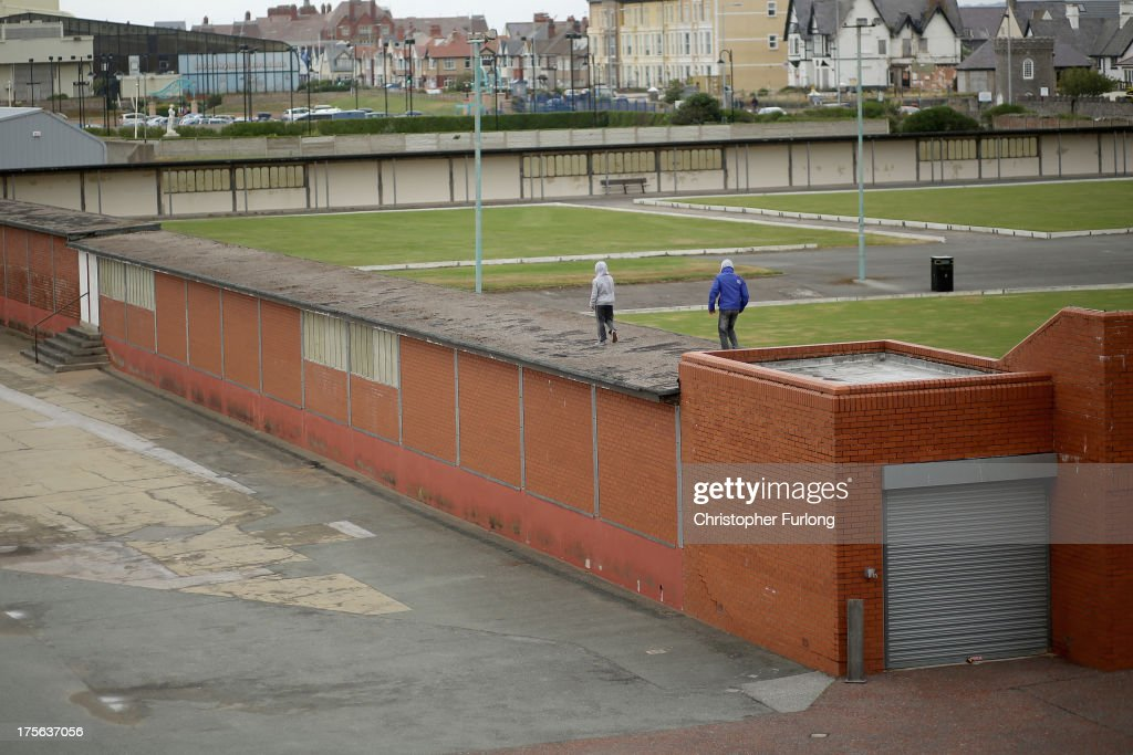 Youths walk along the roof of Rhyl bowling club on August 5, 2013 in Rhyl, Wales. The think tank The Centre for Social Justice (CSJ) has today said that some British seaside towns such as Rhyl in North Wales were becoming 'dumping grounds' for vulnerable people. The report 'Turning the Tide' has monitored conditions in five seaside towns, Rhyl in Denbighshire, Margate in Kent, Clacton-on-Sea in Essex, Blackpool in Lancashire and Great Yarmouth in Norfolk. In one area of Rhyl, over 66% of working-age people were found to be dependent on out-of-work benefits.