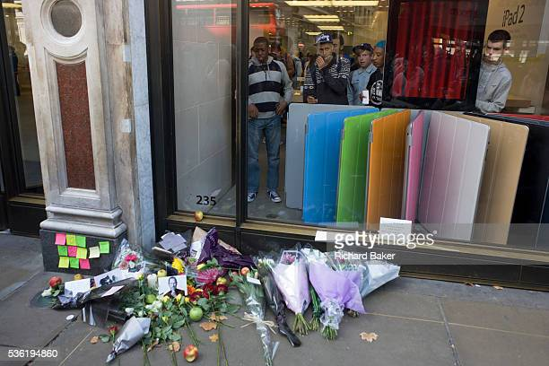 Youths watch passersby from inside London's Apple store where a makeshift shrine has been formed where Londoners commemorate Apple's creator Steve...