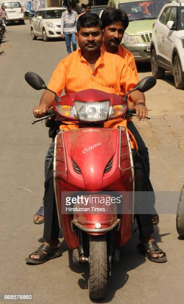 Youths wearing saffron color shirts on April 13 2017 in Lucknow India After the thumping victory of Bharatiya Janata Party in assembly polls donning...