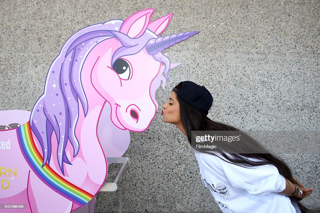 YouTuber Lilly Singh poses with a unicorn during VidCon at the Anaheim Convention Center on June 23 2016 in Anaheim California