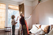 Senior man is helping his wife with the housework. He is using an extended feather duster to clean the ceiling and his wife is pointing out areas he has missed.