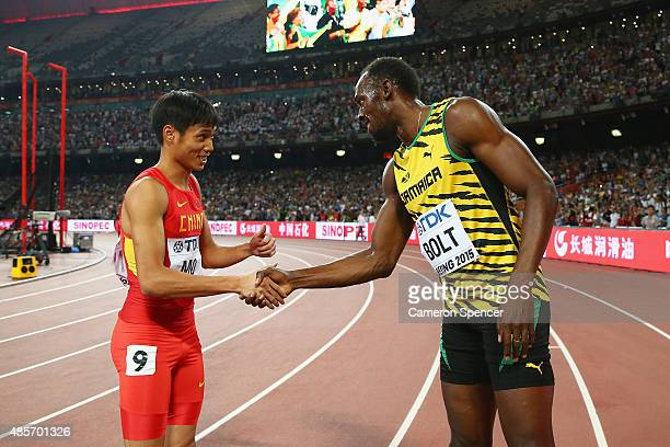 Youxue Mo of China shakes hands with Usain Bolt of Jamaica after the Men's 4x100 Metres Relay final during day eight of the 15th IAAF World Athletics...