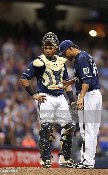 Yovani Gallardo of the Milwaukee Brewers and Martin Maldonado wait for a coaching visit on the mound with the bases loaded during the fourth inning...