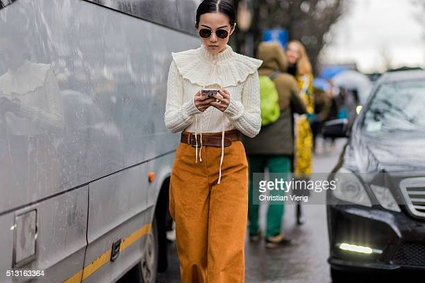Yoyo Cao is wearing round sunglasses a creme jumper bronze wide pants and a brown belt seen outside Giorgio Armani during Milan Fashion Week...