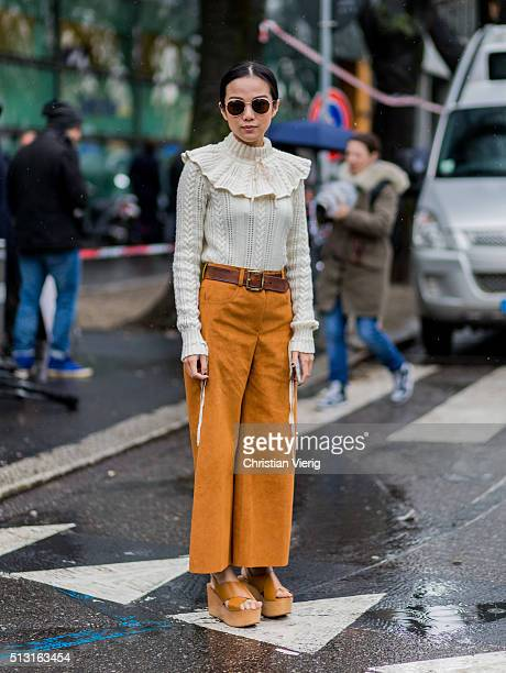Yoyo Cao is wearing round sunglasses a creme jumper bronze wide pants and a brown belt and platform sandals seen outside Giorgio Armani during Milan...