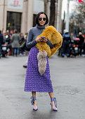 Yoyo Cao wearing a yellow fur scarf and grey turtleneck and purple skirt outside Miu Miu during the Paris Fashion Week Womenswear Fall/Winter...