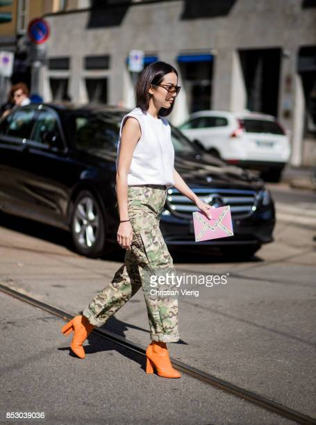 Yoyo Cao wearing orange ankle boots is seen outside Dolce Gabbana during Milan Fashion Week Spring/Summer 2018 on September 24 2017 in Milan Italy