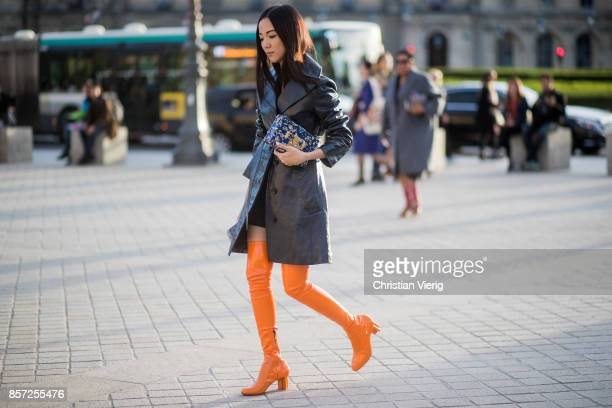 Yoyo Cao wearing orange overknee boots black leather coat seen outside Louis Vuitton during Paris Fashion Week Spring/Summer 2018 on October 3 2017...