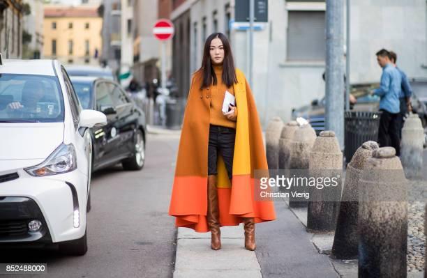 Yoyo Cao wearing orange yellow red cape orange turtleneck denim jeans overknees is seen outside Bottega Veneta during Milan Fashion Week...