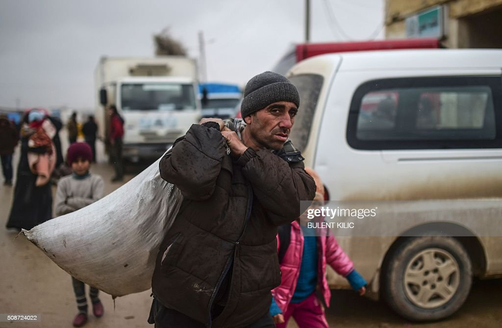 A yrefugee carrying belongings arrives at the Turkish border crossing gate as Syrians fleeing the northern embattled city of Aleppo wait on February 6, 2016 in Bab-Al Salam, near the city of Azaz, northern Syria. Thousands of Syrians were braving cold and rain at the Turkish border Saturday after fleeing a Russian-backed regime offensive on Aleppo that threatens a fresh humanitarian disaster in the country's second city. Around 40,000 civilians have fled their homes over the regime offensive, according to the Syrian Observatory for Human Rights monitor. / AFP / BULENT KILIC