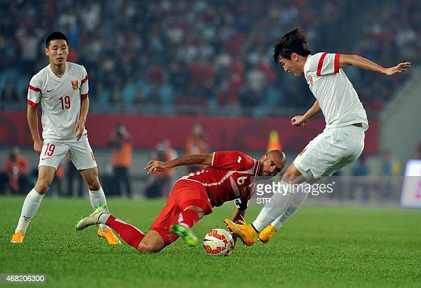 Yu Dabao of China tussles for the ball against Houcine Ragued of Tunisia during a football friendly match in Nanjing east China's Jiangsu province on...