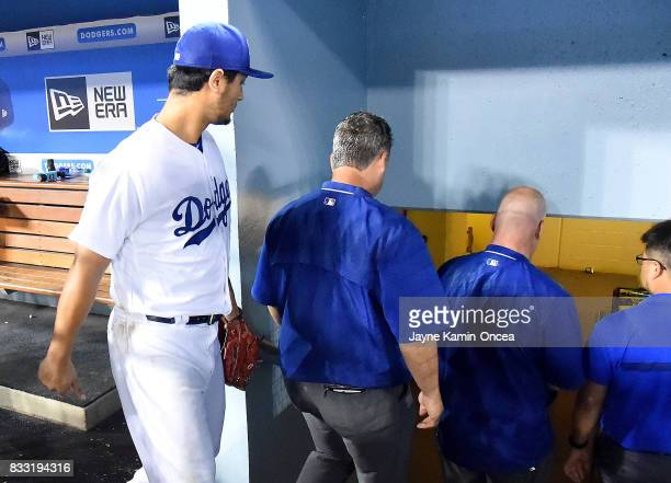 Yu Darvish of the Los Angeles Dodgers follows team trainers as he leaves the dugout in the seventh inning of the game against the Chicago White Sox...