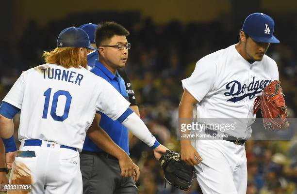 Yu Darvish of the Los Angeles Dodgers gets some encouragement from Justin Turner as he leaves the game at the start of the seventh inning against the...