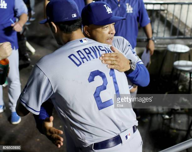 Yu Darvish of the Los Angeles Dodgers is congratulated by manager Dave Roberts after Darvish came into the dugout after the seventh inning against...