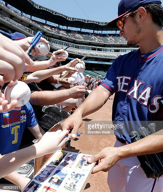 Yu Darvish of the Texas Rangers autographs baseball memorbila for fans before a baseball game against the Toronto Blue Jays at Globe Life Park on May...