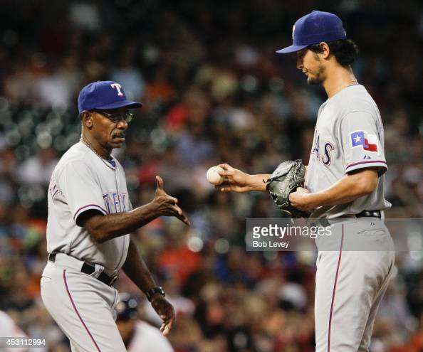 Yu Darvish of the Texas Rangers gives the ball to manager Ron Washington as he leaves the game in the fifth inning against the Houston Astros at...