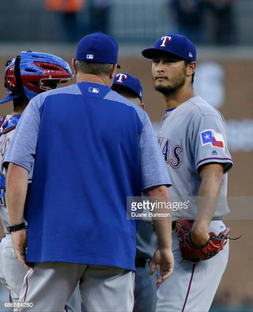 Yu Darvish of the Texas Rangers is visited on the mound by pitching coach Doug Brocail of the Texas Rangers during the first inning of a game against...