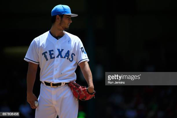 Yu Darvish of the Texas Rangers pauses between throws as the Rangers take on the Seattle Mariners during the first inning at Globe Life Park in...