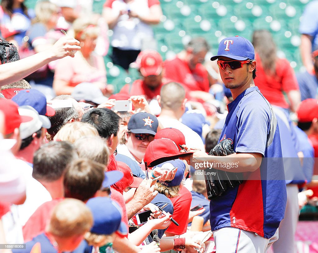 Yu Darvish #11 of the Texas Rangers signs autographs before the Texas Rangers play the Houston Astros at Minute Maid Park on May 12, 2013 in Houston, Texas.