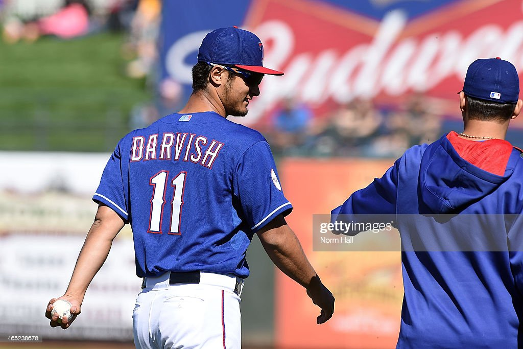 <a gi-track='captionPersonalityLinkClicked' href=/galleries/search?phrase=Yu+Darvish&family=editorial&specificpeople=4018539 ng-click='$event.stopPropagation()'>Yu Darvish</a> #11 of the Texas Rangers talks to a teammate while walking back to the clubhouse after the fourth inning of a game against the Kansas City Royals on March 4, 2015 in Surprise, Arizona.