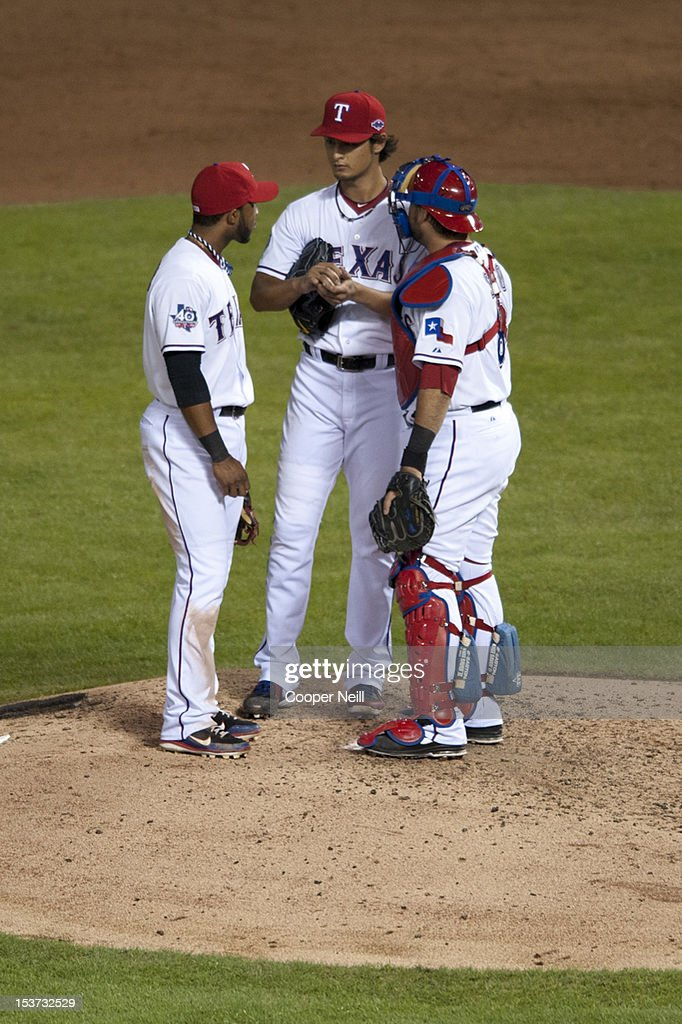 Yu Darvish #11 of the Texas Rangers talks with teammates Elvis Andrus #1 and Geovany Soto #8 during the American League Wild Card game against the Baltimore Orioles on October 5, 2012 at the Rangers Ballpark in Arlington, Texas.