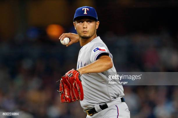Yu Darvish of the Texas Rangers throws to first base to check on a New York Yankees base runner during the first inning at Yankee Stadium on June 23...