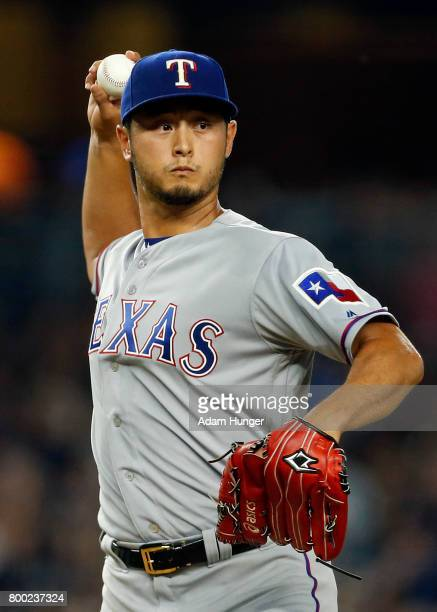 Yu Darvish of the Texas Rangers throws to first base to check on a baserunner against the New York Yankees during the second inning at Yankee Stadium...