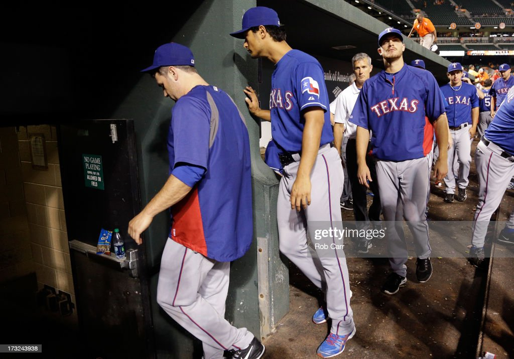 Yu Darvish #11 of the Texas Rangers (C) walks to the clubhouse following the Rangers 6-1 loss to the Baltimore Orioles at Oriole Park at Camden Yards on July 10, 2013 in Baltimore, Maryland.