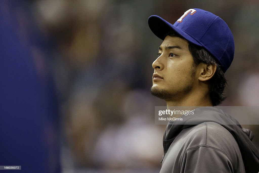 Yu Darvish #11 of the Texas Rangers watches the game from the edge of the Rangers dugout before the strat of the game against the Milwaukee Brewers at Miller Park on May 08, 2013 in Milwaukee, Wisconsin.