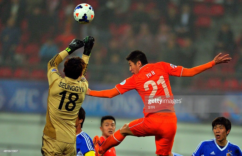 Yu Hai (R) of China's Guizhou Renhe tussles for the ball against goalkeeper Kim Seung-gyu of South Korea's Ulsan Hyundai during their AFC Champions League group H first round match at the Guiyang Olympic Centre Stadium, in Guiyang, Guizhou province on April 1, 2014. Renhe beat Ulsan 3-1. CHINA