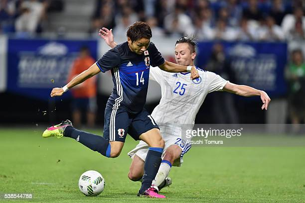 Yu Kobayashi of Japan is challenged by Almir Bekic of Bosnia and Herzegovina during the international friendly match between Japan and Bosnia and...