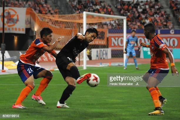 Yu Kobayashi of Kawasaki Frontale controls the ball under pressure of Naoki Kawaguchi and Rony of Albirex Niigata during the JLeague J1 match between...