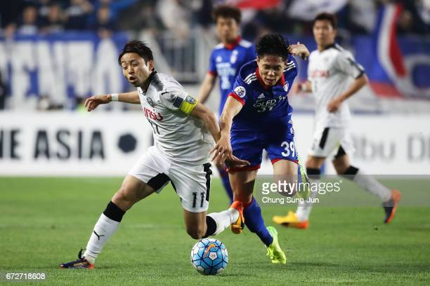Yu Kobayashi of Kawasaki Frontale cpmtepes for the ball with Min SangKi of Suwon Samsung Bluewings during the AFC Champions League Group G match...