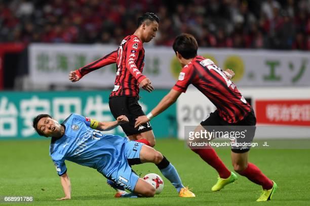 Yu Kobayashi of Kawasaki Frontale is challenged by Takuma Arano of Consadole Sapporo during the JLeague J1 match between Consadole Sapporo and...
