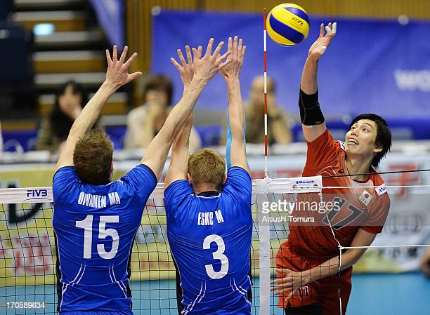 Yu Koshikawa of Japan spikes the ball against Mikko Esko and Matti Oivanen of Finland during the FIVB World League Pool C match between Japan and...