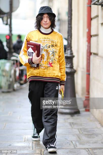 Yu Masui wears a black hat a white turtleneck pull over a bomber jacket black sportswear pants and a clutch designed as a Marlboro smokes box with...