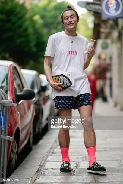 Yu Masui wears a white tshirt with the word 'Goth' prined in pink a clutch a short pink socks sandals and s holding an ice cream outside the Dries...