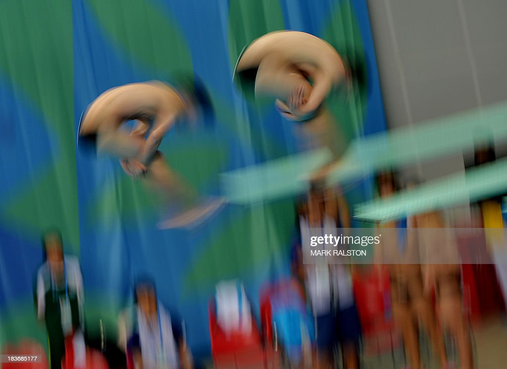 Yu Okamoto (L) and Hiroto Hasegawa (R) compete before winning gold in the Men's Synchronized 3m Springboard Final at the East Asian Games held at the Tianjin Olympic Center Diving Hall in Tianjin on October 9, 2013. The East Asian Games which are held every four years see nine countries including China, Japan, South and North Korea participating in 262 events in 22 different sports. AFP PHOTO / Mark RALSTON