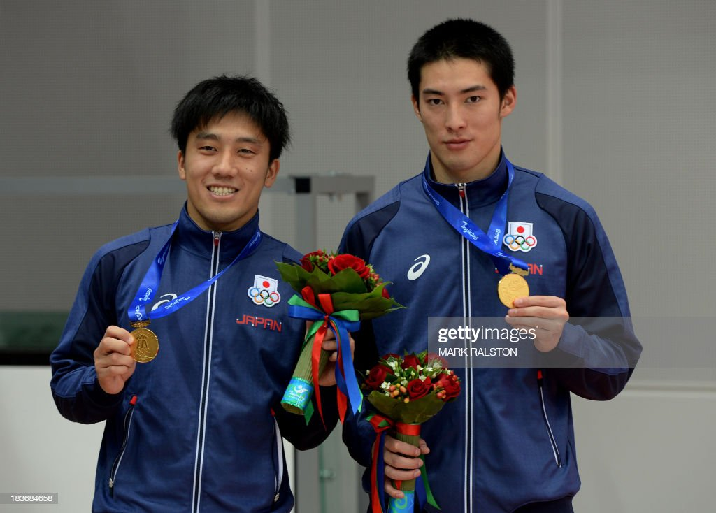 Yu Okamoto (L) and Hiroto Hasegawa (R) of Japan celebrate after winning gold in the Men's Synchronized 3m Springboard Final at the East Asian Games held at the Tianjin Olympic Center Diving Hall in Tianjin on October 9, 2013. The East Asian Games which are held every four years see nine countries including China, Japan, South and North Korea participating in 262 events in 22 different sports. AFP PHOTO / Mark RALSTON