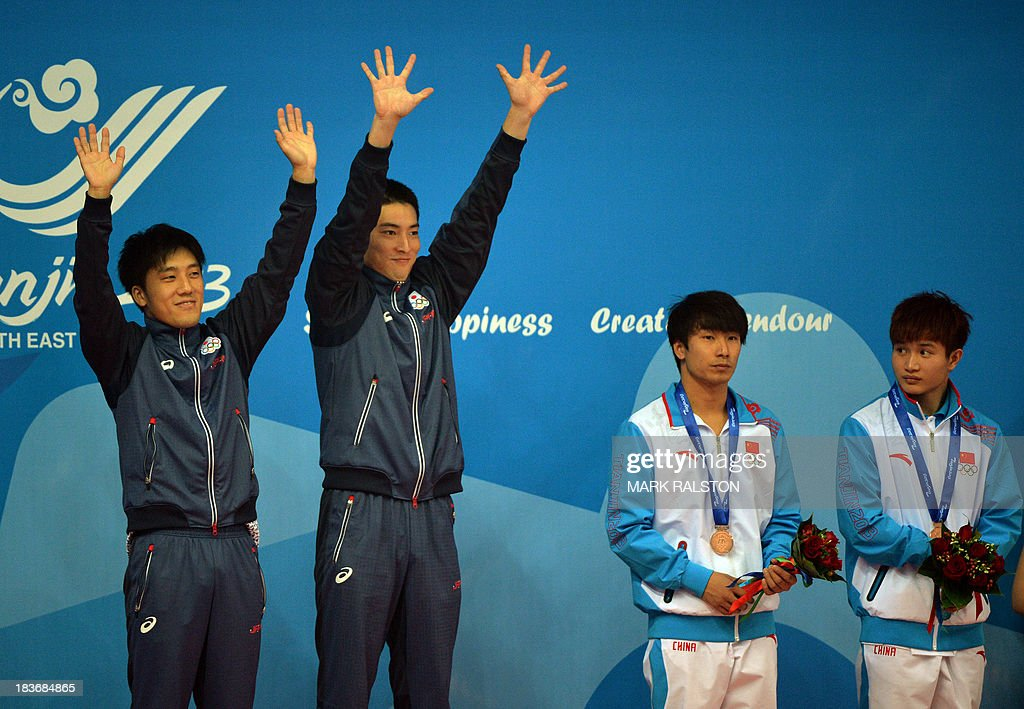 Yu Okamoto (L) and Hiroto Hasegawa (2nd L) of Japan celebrate beside third place Li Jincong (2nd R) and Cai Chengcheng of China after winning gold in the Men's Synchronized 3m Springboard Final at the East Asian Games held at the Tianjin Olympic Center Diving Hall in Tianjin on October 9, 2013. The East Asian Games which are held every four years see nine countries including China, Japan, South and North Korea participating in 262 events in 22 different sports. AFP PHOTO / Mark RALSTON