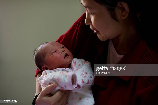Yu Qiuyan holds her newborn baby girl Li Muhua in her room at the Antai maternity hospital in Beijing on January 26 2012 As China welcomes the year...