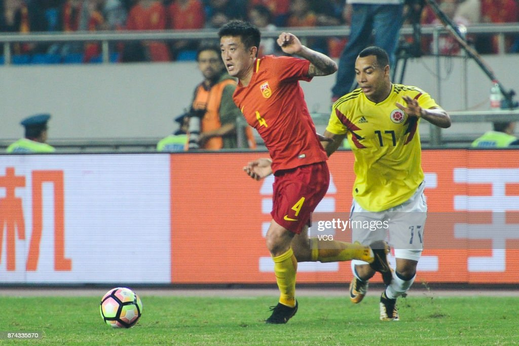 Yu Tamura #17 of Columbia National Team and Jiang Zhipeng #4 of China National Team compete for the ball during the international friendly match between China and Columbia at Chongqing Olympic Sports Centre on November 14, 2017 in Chongqing, China.
